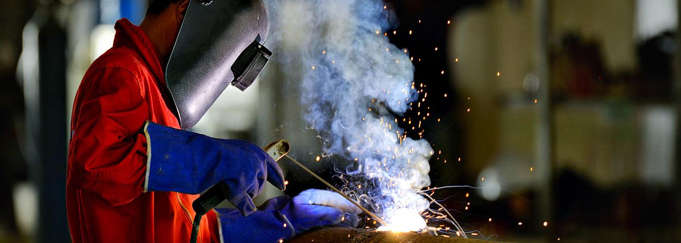 Worker welding on shop floor